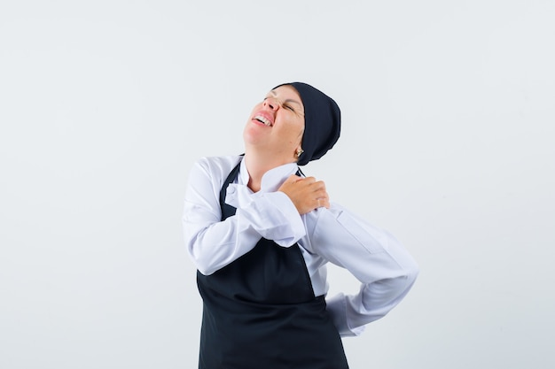 Vrouwelijke kok in uniform, schort die aan rugpijn lijdt en vermoeid kijkt, vooraanzicht.
