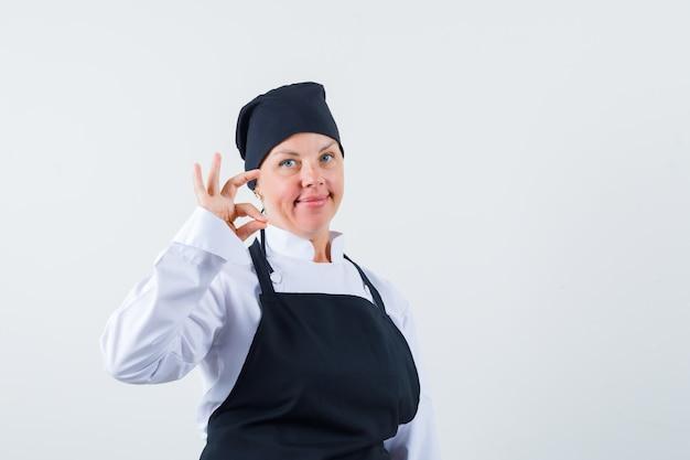 Vrouwelijke kok in uniform, schort die ok gebaar toont en zelfverzekerd kijkt, vooraanzicht.
