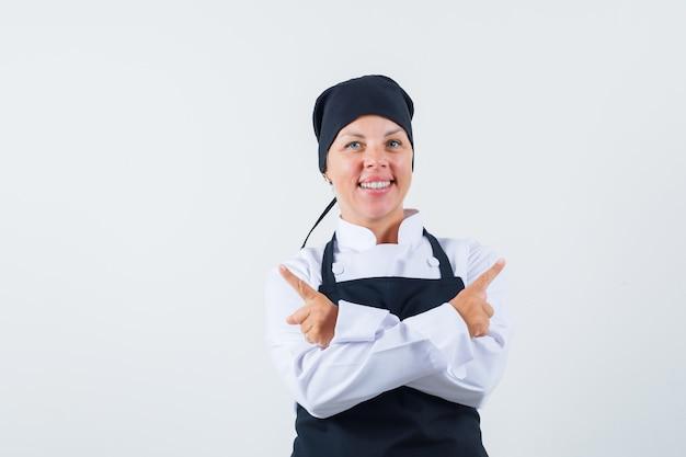 Vrouwelijke kok in uniform, schort die weg wijst en er vrolijk uitziet, vooraanzicht.