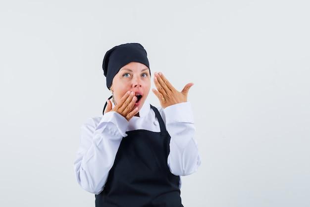 Vrouwelijke kok in uniform, schort hand in hand in de buurt van open mond en op zoek verrast, vooraanzicht.