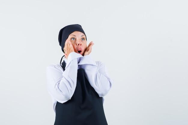 Vrouwelijke kok in uniform, schort hand in hand op de wangen en op zoek naar verwonderd, vooraanzicht.