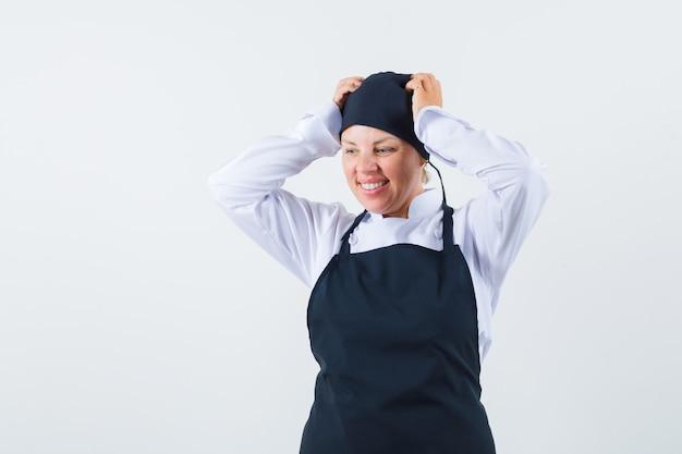 Vrouwelijke kok in uniform, schort hand in hand op het hoofd en kijkt opgewonden, vooraanzicht.