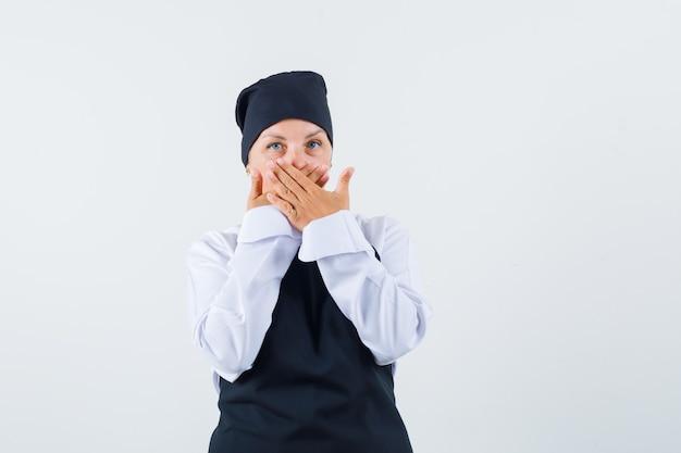 Vrouwelijke kok in uniform, schort hand in hand op mond en op zoek verrast, vooraanzicht.