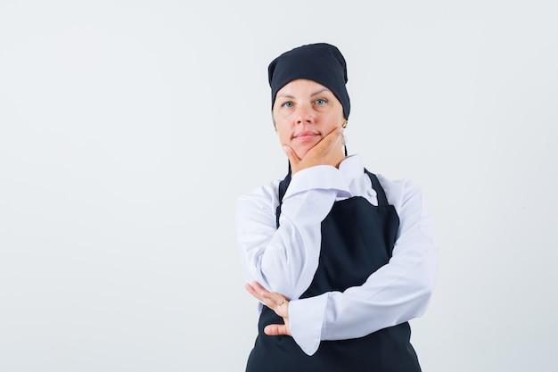 Vrouwelijke kok in uniform, schort hand op kin en op zoek verstandig, vooraanzicht.
