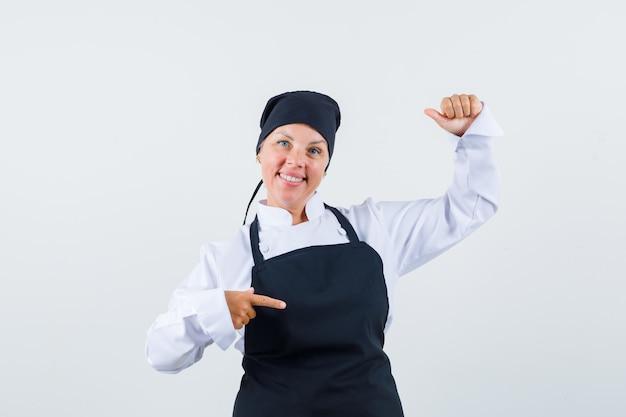 Vrouwelijke kok in uniform, schort opzij wijzend, net alsof ze iets vasthoudt en er vrolijk uitziet, vooraanzicht.