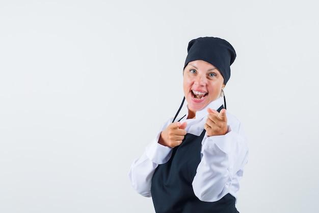 Vrouwelijke kok in uniform, schort wijzend op camera en op zoek gelukkig, vooraanzicht.