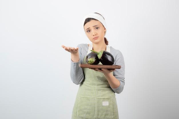 Vrouwelijke kok met plaat van grote aubergines op wit.