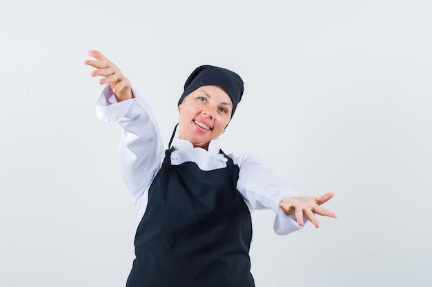 Vrouwelijke kok opent armen voor knuffel in uniform, schort en ziet er schattig uit, vooraanzicht.