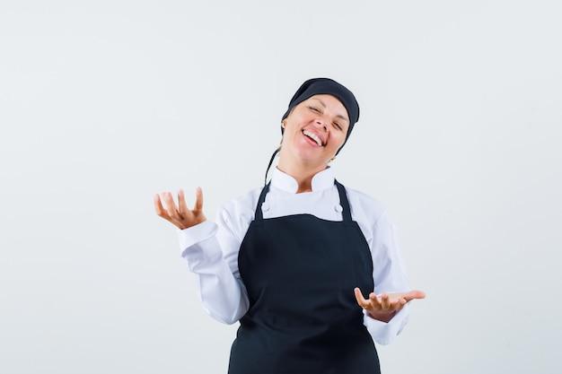 Vrouwelijke kok schalen gebaar maken in uniform, schort en vrolijk kijken. vooraanzicht.