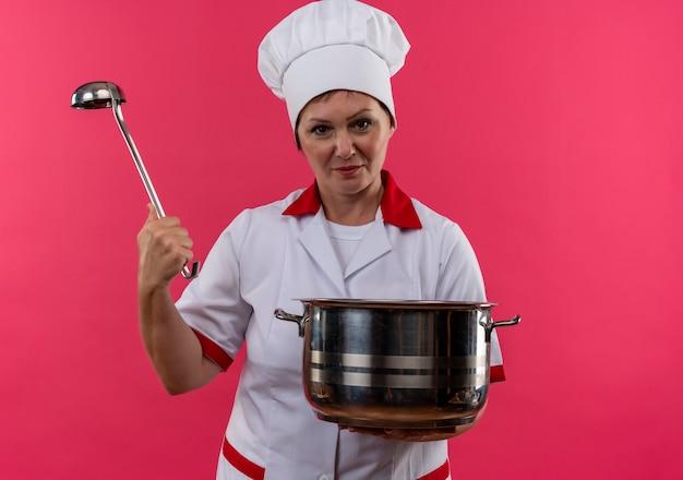 Vrouwelijke kok van middelbare leeftijd in de steelpan en de pollepel van de chef-kok eenvormige holding op geïsoleerde roze muur Gratis Foto