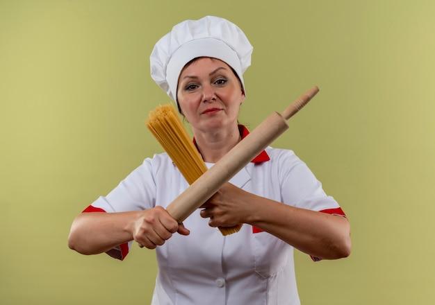 Vrouwelijke kok van middelbare leeftijd in uniforme chef-kok kruising deegroller en spaghetti in haar handen op geïsoleerde groene muur