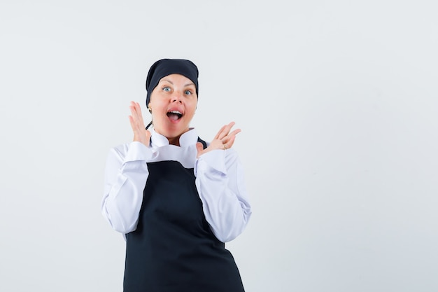 Vrouwelijke kok verhogen handen in uniform, schort en opgewonden kijken. vooraanzicht.