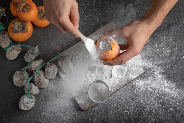 Vrouwelijke kok voegt bloem toe aan zoete persimmon in de keuken