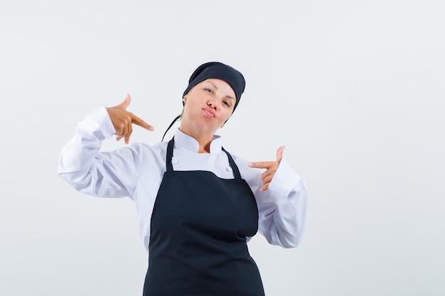 Vrouwelijke kok wijst naar zichzelf in uniform, schort en kijkt zelfverzekerd, vooraanzicht.