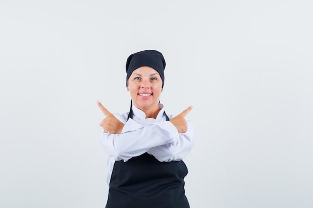 Vrouwelijke kok wijst weg in uniform, schort en kijkt zelfverzekerd. vooraanzicht.