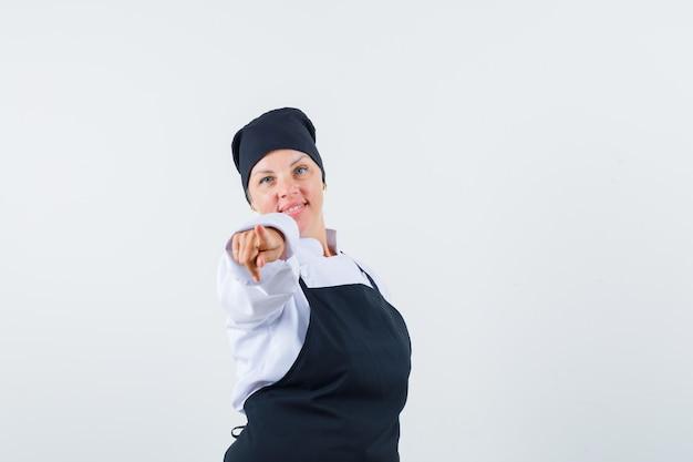 Vrouwelijke kok wijzend op camera in uniform, schort en kijkt zelfverzekerd, vooraanzicht.