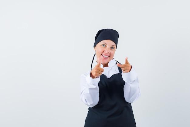 Vrouwelijke kok wijzend op camera in uniform, schort en op zoek vrolijk, vooraanzicht.