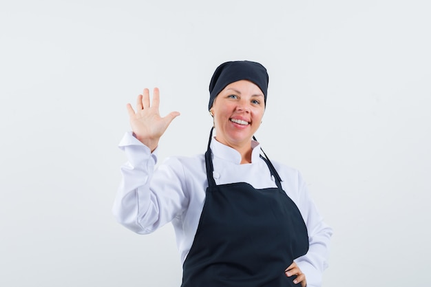 Vrouwelijke kok zwaait met de hand om afscheid te nemen in uniform, schort en ziet er vrolijk uit. vooraanzicht.