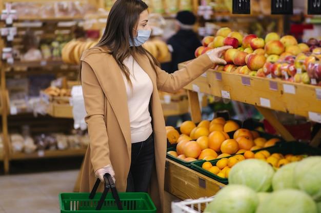 Vrouwelijke koper die een beschermend masker en handschoenen in supermarkt draagt. winkelen tijdens de pandemische quarantaine. vrouw die vers fruit koopt