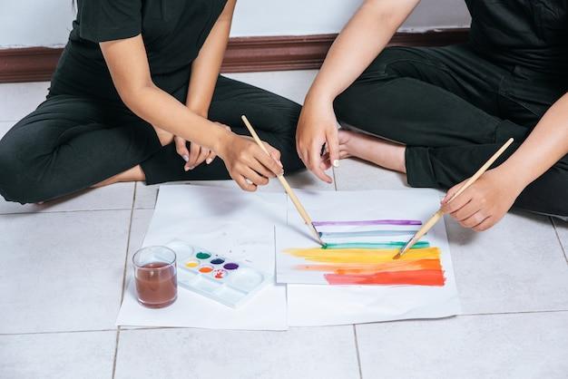 Vrouwelijke koppels tekenen en schilderen op papier.