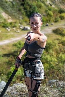 Vrouwelijke krijger poseren met machete op buiten. zomer levensstijl