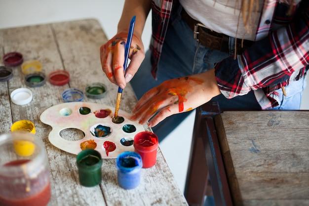 Vrouwelijke kunstenaar die binnen schildert