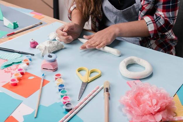Vrouwelijke kunstenaar die brief van witte klei voorbereidt