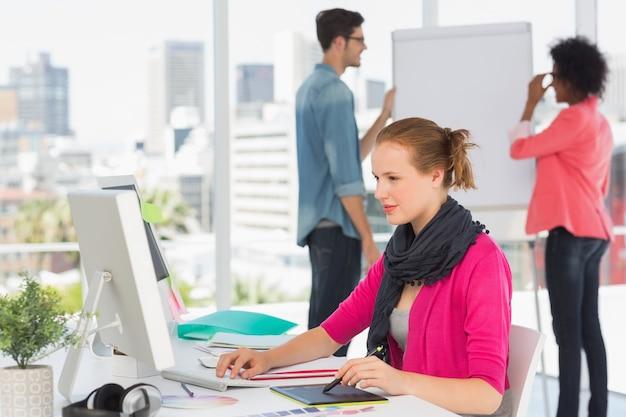 Vrouwelijke kunstenaar die grafische tablet met collega's op kantoor gebruiken