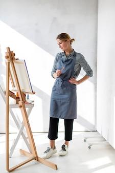 Vrouwelijke kunstenaar die het schilderen bekijkt
