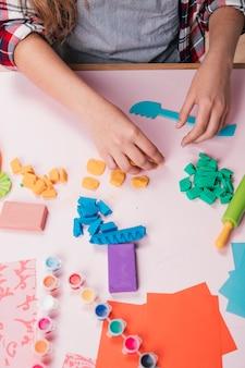 Vrouwelijke kunstenaar die kleurrijk kleistuk over bureau houdt