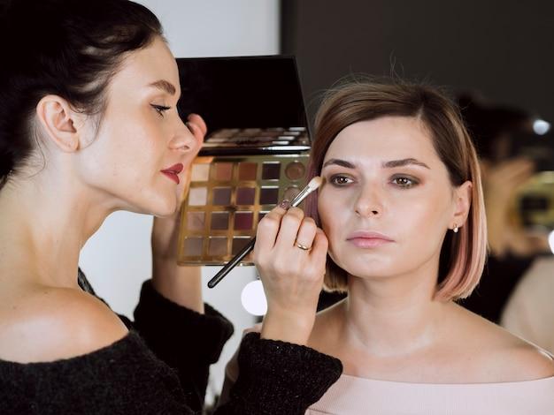 Vrouwelijke kunstenaar die make-up op model toepast