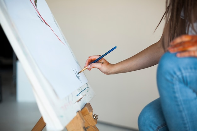 Vrouwelijke kunstenaar die op canvas in studio schildert