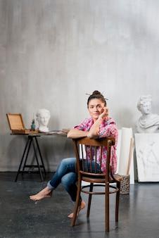 Vrouwelijke kunstenaar op stoel