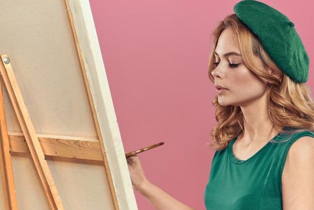 Vrouwelijke kunstenaar schildert een afbeelding op canvas met een ezel