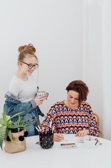 Vrouwelijke kunstenaar schildert terwijl haar dochter toekijkt