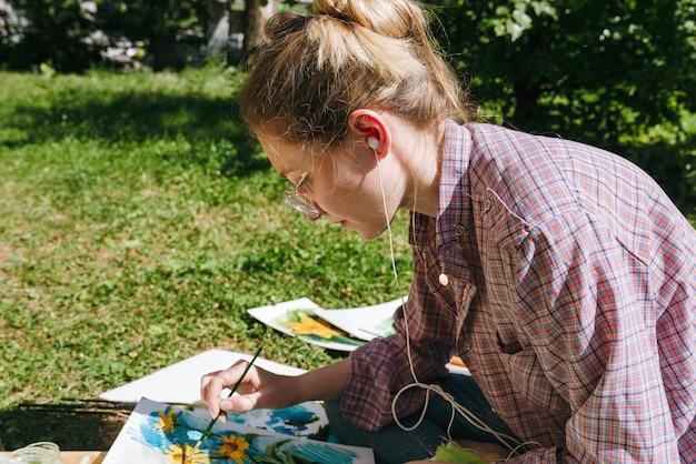 Vrouwelijke kunstenaar tekenen van bloemen met olieverf buitenshuis, schilder