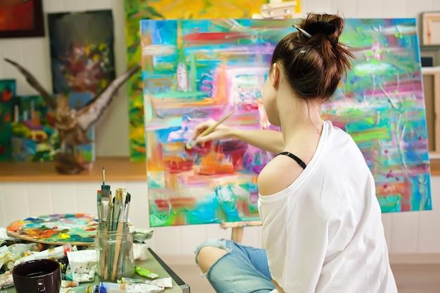 Vrouwelijke kunstenaar working on painting in studio.