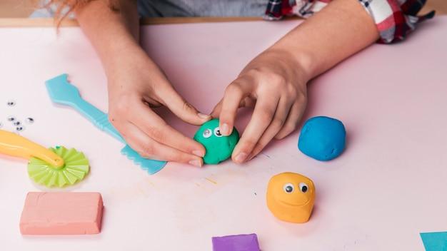 Vrouwelijke kunstenaarshand die beeldverhaalgezichten maken die zachte klei gebruiken