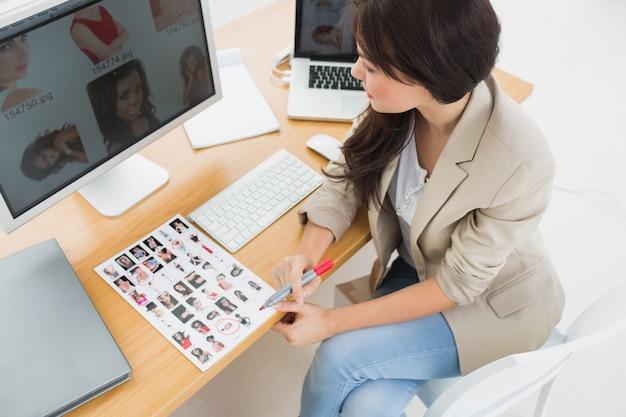 Vrouwelijke kunstenaarszitting bij bureau met computers in bureau