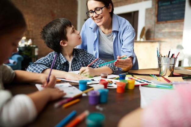 Vrouwelijke kunstleraar werken met kinderen