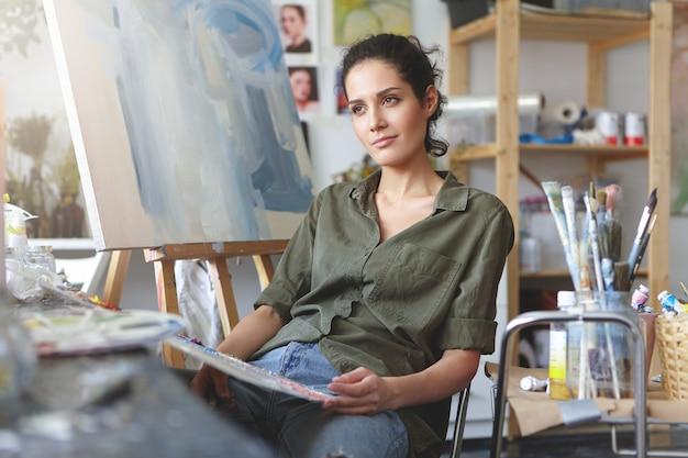 Vrouwelijke kunstliefhebber maakt voorlopige schetsen en probeert zich haar toekomstige meesterwerk voor te stellen, met een doordachte uitdrukking omringd door kunstreproducties.