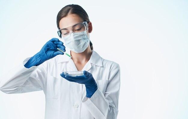 Vrouwelijke laboratoriumassistent in een medisch masker met een scheikundig element in een kolf-vaccinatie