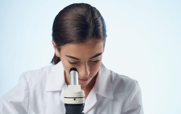 Vrouwelijke laboratoriumassistent in medische handschoenen en een kolf met vloeibare scheikundig element microscoop.
