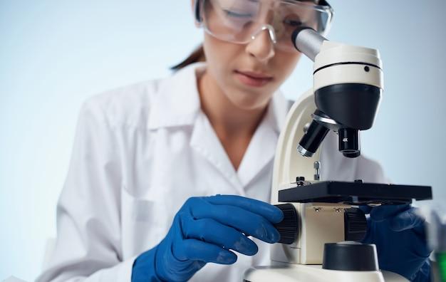 Vrouwelijke laboratoriumassistent onderzoekt bacteriën door een microscoop en een bril op de vaccinatie van het chemische element van het gezicht.