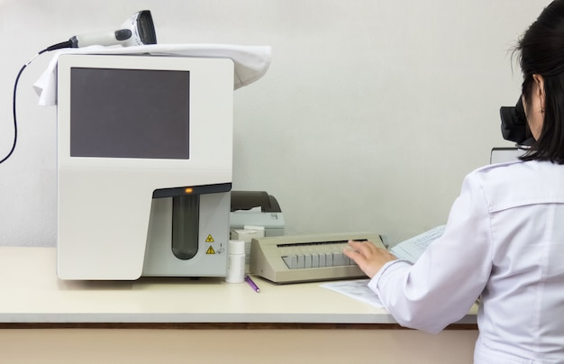 Vrouwelijke laboratoriummedewerker die met microscoop werkt. geautomatiseerde hematologische bloedanalysator