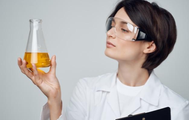 Vrouwelijke laboratoriummedewerker met een kolf in zijn handen bril op zijn gezicht en een medische jurk.