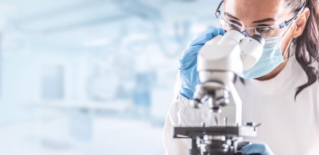 Vrouwelijke laboratoriumtechnicus in beschermende bril en gezichtsmasker zit naast een microscoop in laboratorium