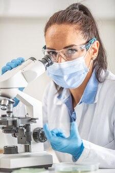Vrouwelijke laboratoriumtechnicus in beschermende bril, handschoenen en gezichtsmasker zit naast een microscoop en erlenmeyer, kijkend in de camera.