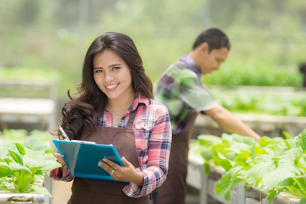 Vrouwelijke landbouwer die in een groen huis werkt