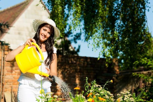Vrouwelijke landbouwer het water geven bloemen in tuin